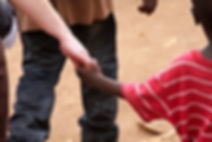 White adult and black child holding hands
