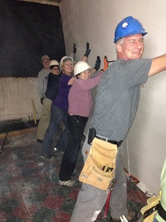 Volunteer and staff moving a wall in the new location