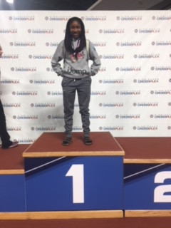 Mollie Speights standing on top of the winner's podium.