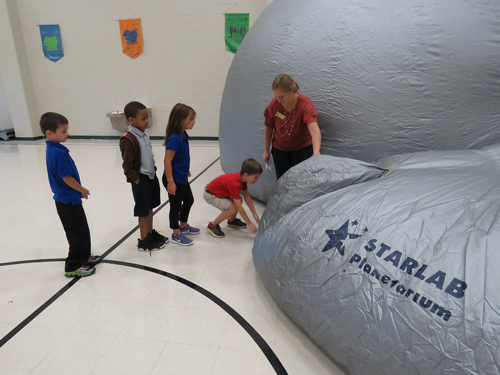 Students crawling into the StarLab entry way.