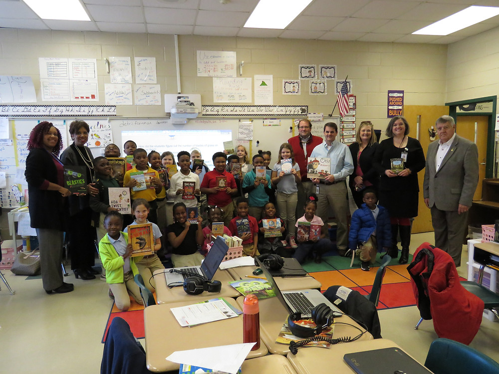 Dr. Price and fellow Rotarians pause for a photo with a third grade class at Lakeview Academy during their donation.