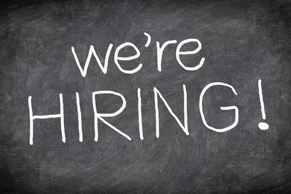 A graphic that says we're hiring on a chalkboard