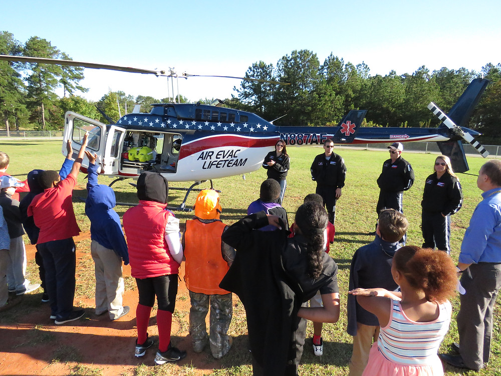 MHA students talking with the air evac lifeteam outside near the helicopter.