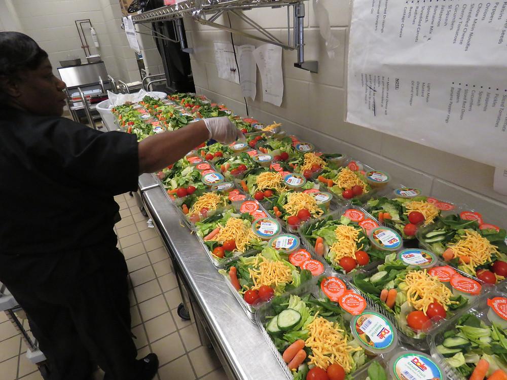 School nutrition employee making salads.