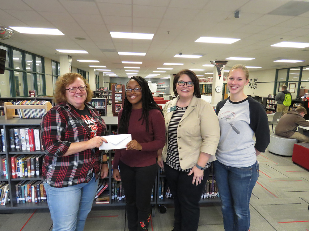 Susan McGill handing the check over to Alexis Roberson who is flanked by the two other members of her team.