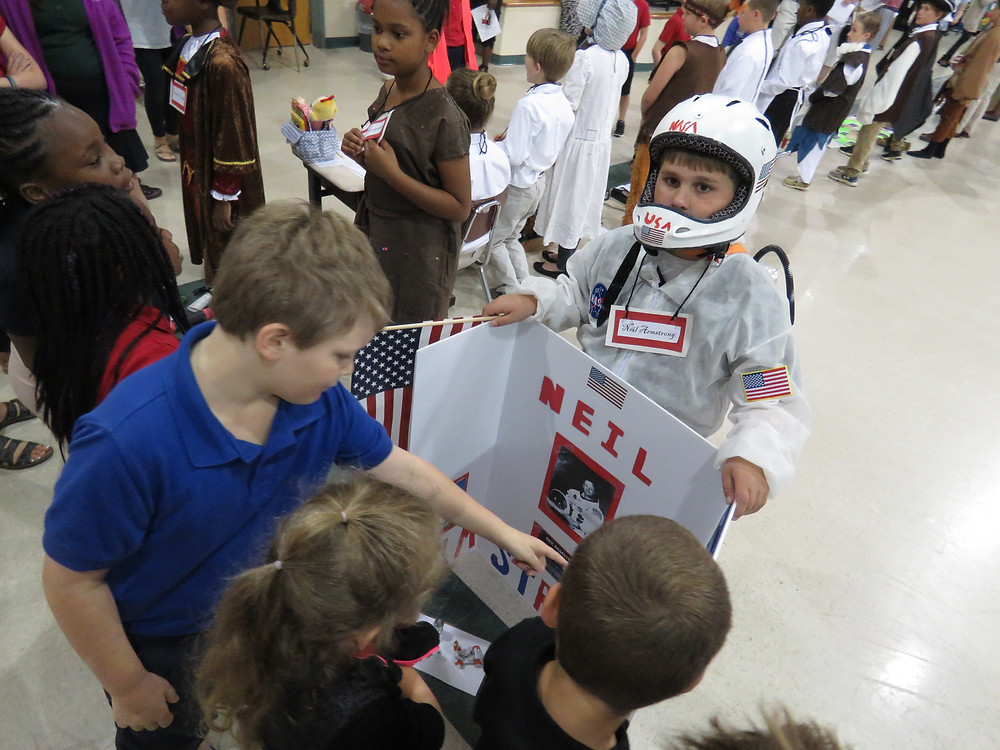 Student dressed as Neil Armstrong talking with other students.