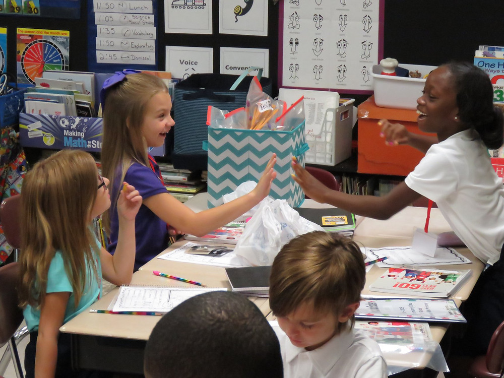 PIcture of students having fun in classroom on their first day of school.