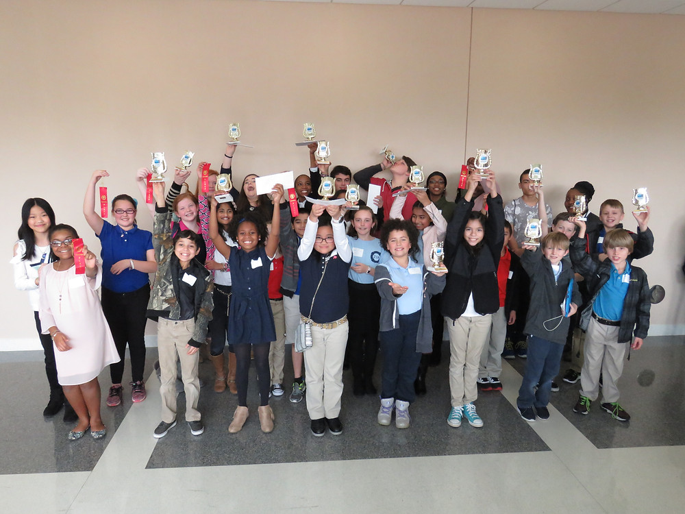 All technology fair winners from all of our schools posing just outside the event with their medals and ribbons.