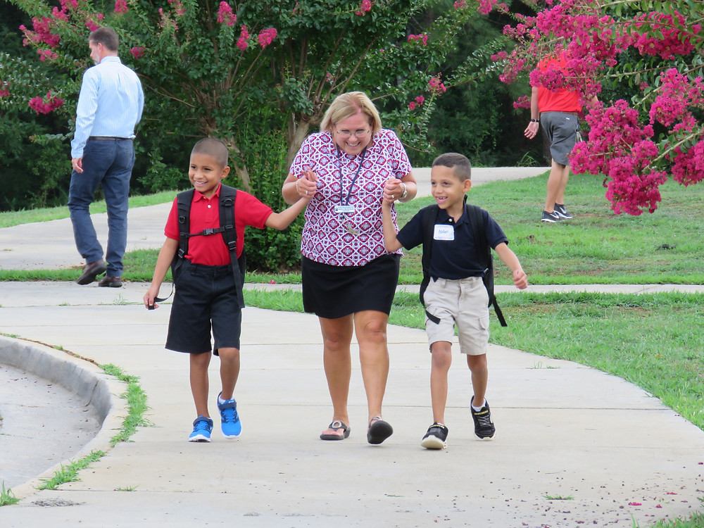 Teacher and students walking together during dismissal.