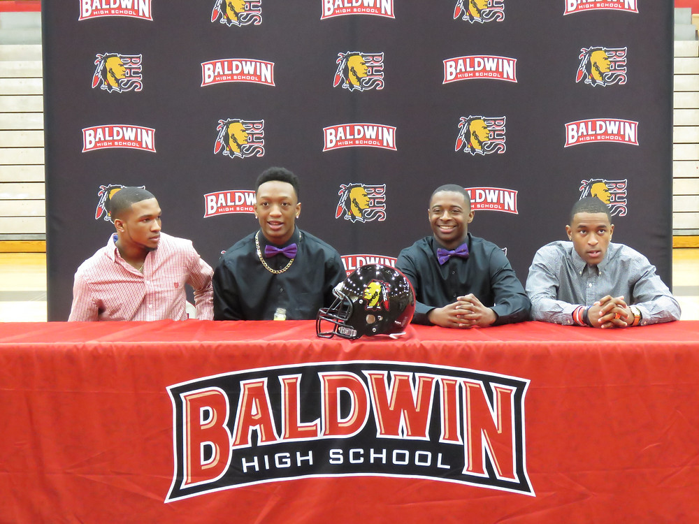 Four Braves football players at signing day.