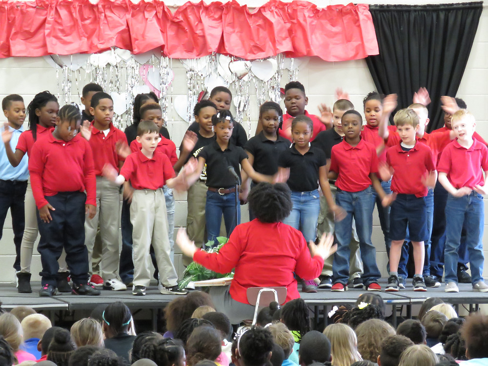 Students on stage signing a song during the performance.