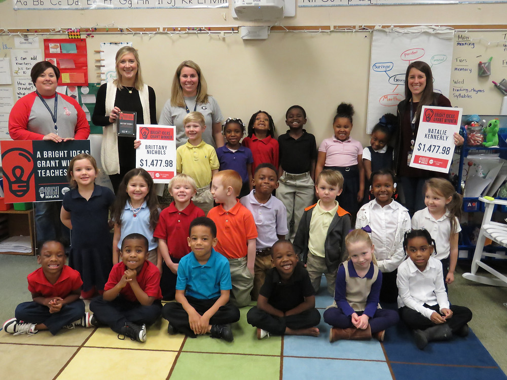 Teachers Natalie Kennerly and Brittany Nichols stand for a group photo with their class and school administrators.