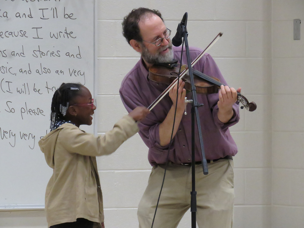 Ken Waldman allows a 4th grade students to help him play the fiddle at his introductory meeting with Midway Hills Academy 4th grade.