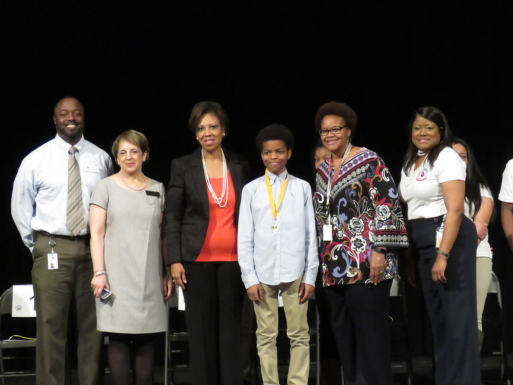 Elijah Rucker flanked by Superintendent Dr. Noris Price, Principal Daymond Ray and other district officials.