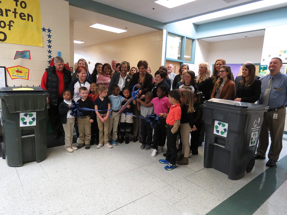 Dr. Price with approximately 40 community members and kindergarten students cutting the ribbon.
