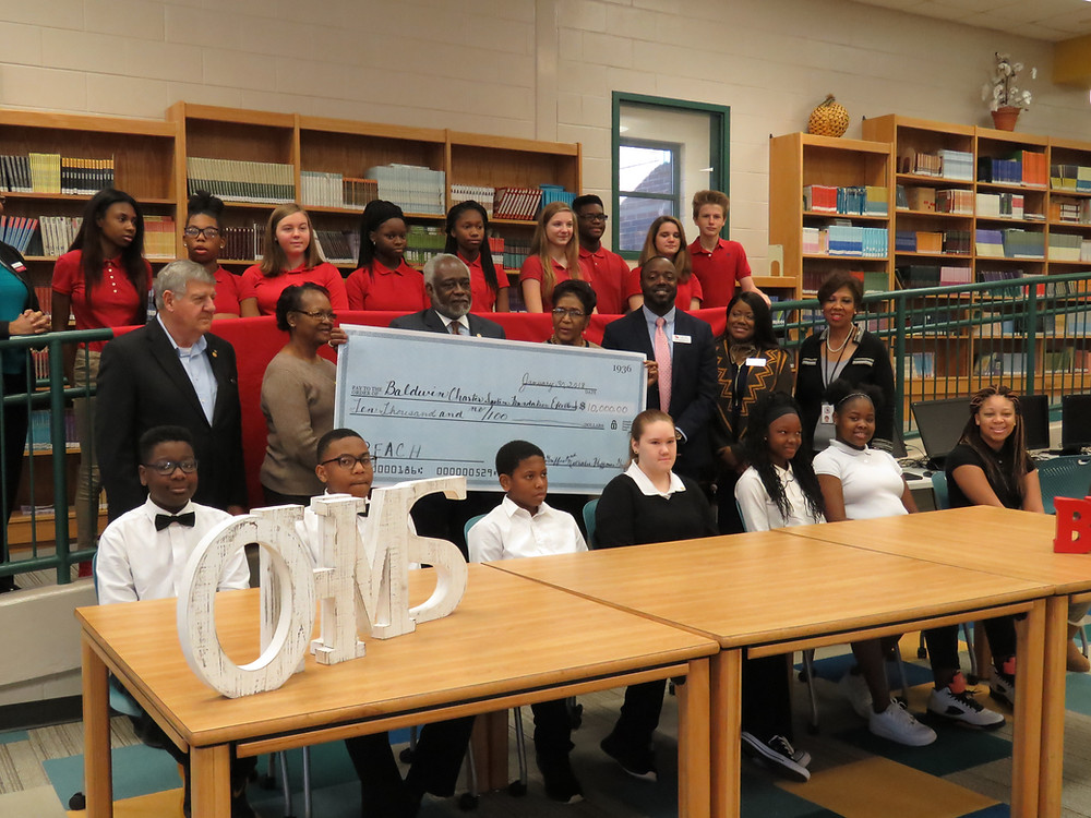 Col. Floyd Griffin & wife Nathalie, flanked by school and district officials, along with REACH scholars at today's check presentation