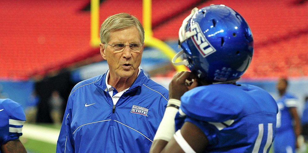 Coach Bill Curry talking with a Georgia State player on the field.