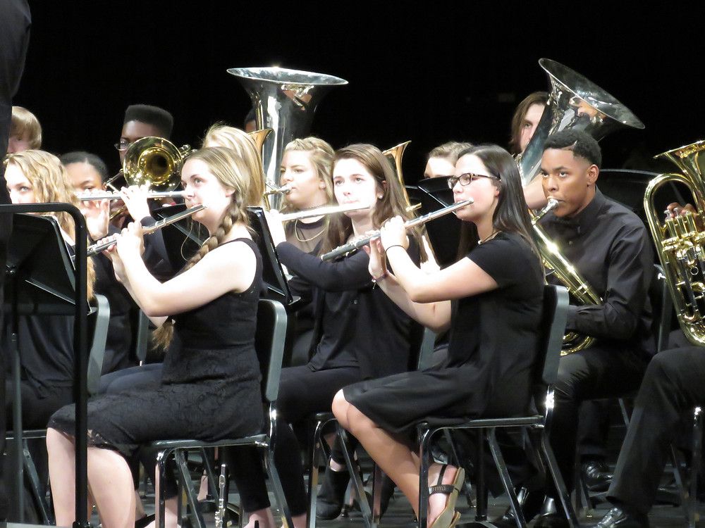 Group shot of students performing in the horns section.