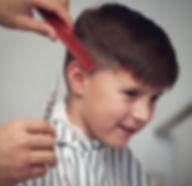 Barber is making haircut to cheerful boy