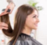 Young beautiful woman having her hair cu