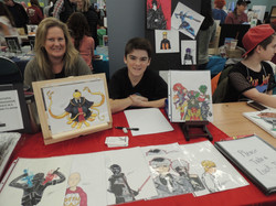 Two youths and adult displaying artwork