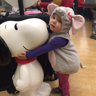 Child dressed as mouse hugging Snoopy