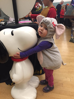 Child dressed as mouse holding Snoopy