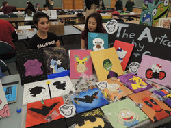 Two youths displaying artwork at a table