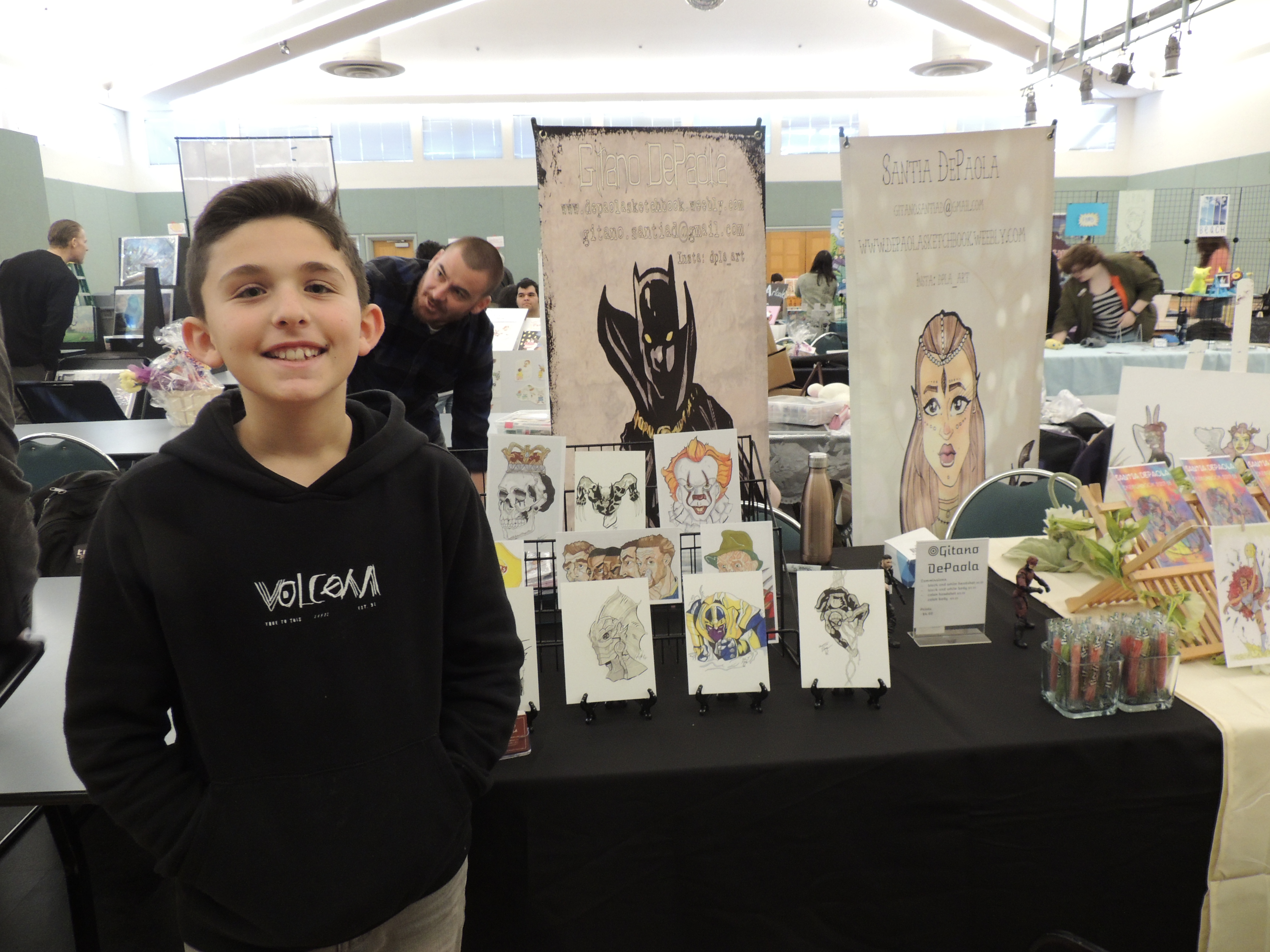 Youth displaying artwork on table