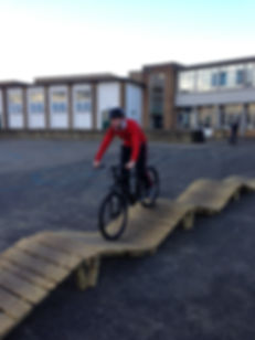 Boy having mtb coaching on bike obstacle course / north shore-style track at school, available for hire.