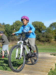 Boy having mtb coaching on bike obstacle course / north shore-style track, available for hire.