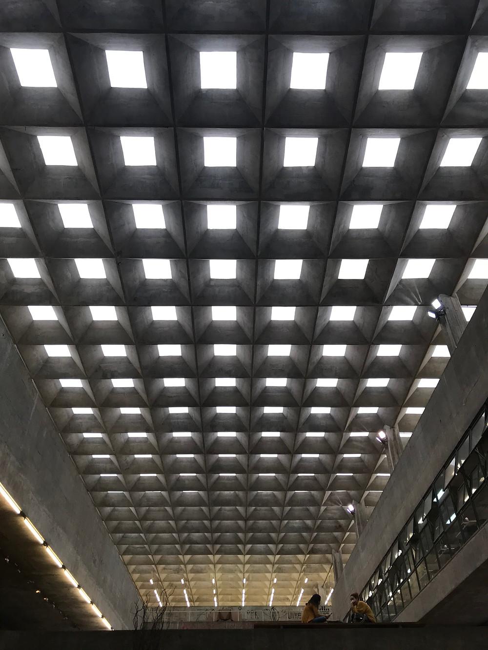 Vista interna da estrutura da cobertura, já recuperada, sobre grande área livre que favorece a integração, com elementos que permitem a iluminação natural