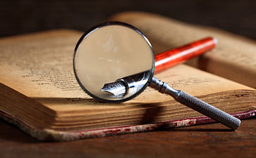 ink-pen-and-magnifying-glass-on-an-old-b