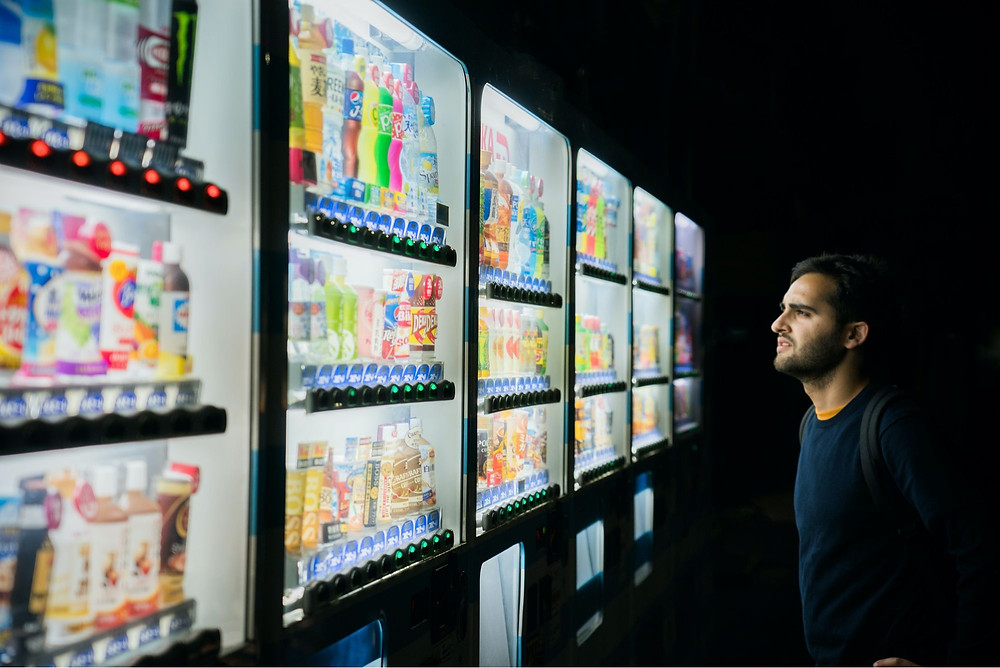 An image of a man standing in front of several drink machines choosing a drink.