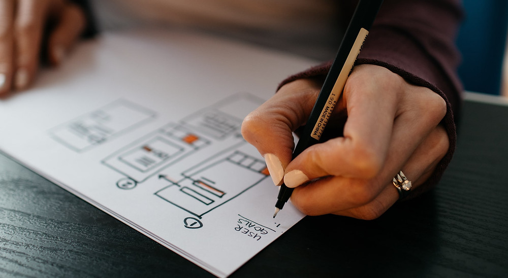 An image of a woman drawing mobile app wireframes.