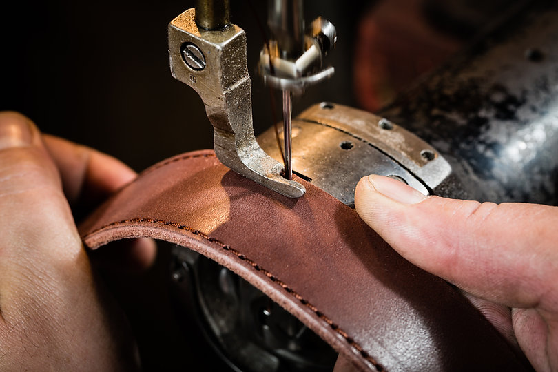 Man's hands behind sewing. Leather workshop.