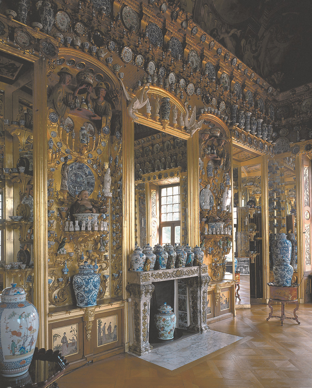 Porcelain cabinent, blue and white porcelain vases, ornate plates on wall. apanese and Chinese  porcelain in front of gilded and mirrored walls.