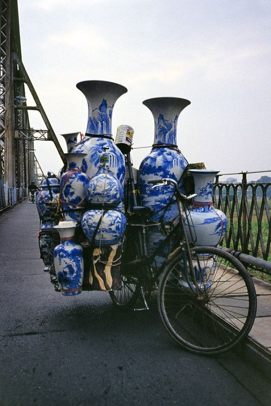 Blue and white porcelain wares attached on a bicycle, ambulant vendor sells Chinese and Vietnamese ceramics, vases, pots in Hanoi, Vietnam