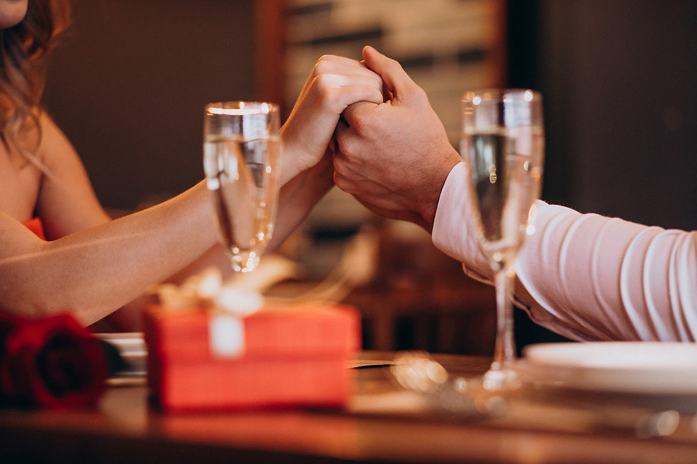 first date, two people holding hands across a fancy restaurant table