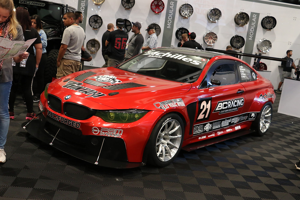 BC racing forged wheels booth at SEMA 2017 with red BMW F82 M4 race car