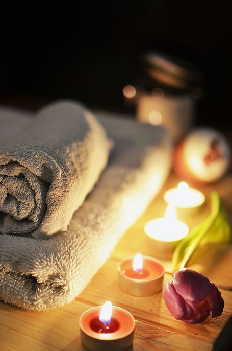 Photo of spa set up with towels, candles and tulip flower
