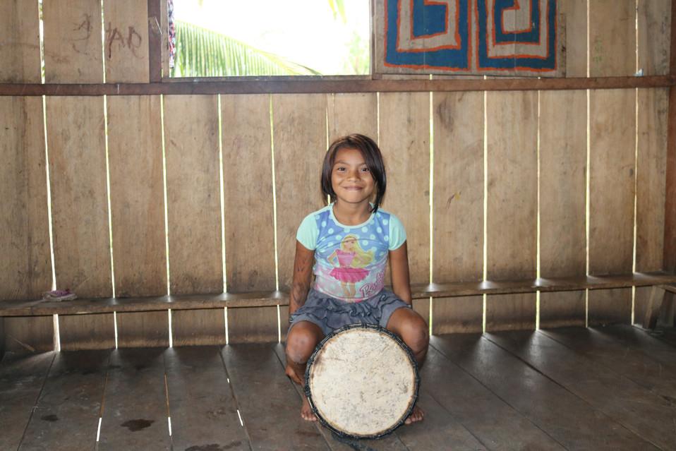 Menina dos povos indígenas Huni Kuin com seu tambor, Acre, Brasil.