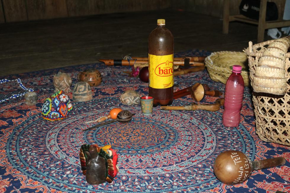 Utensílios para a roda de rapé são colocados no lugar. Estes incluem o rapé, a ayahuasca e flautas.