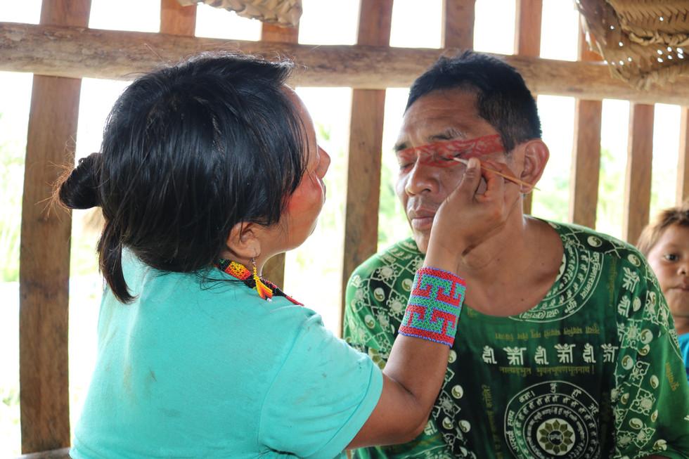 """A pintura de rosto com a cor vermelha do fruto da floresta tropical """"urukum"""" serve como preparação para o ritual."""