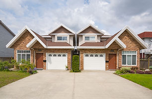 Residential duplex house with concrete drive way and green lawns in front. Two family dwel