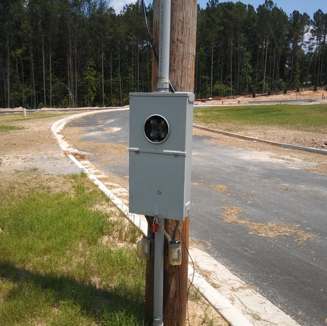 Installation of utility poles and meters on new construction site