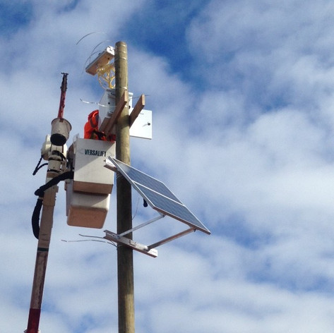 Installation of utility pole, solar panels and camera for security on construction site