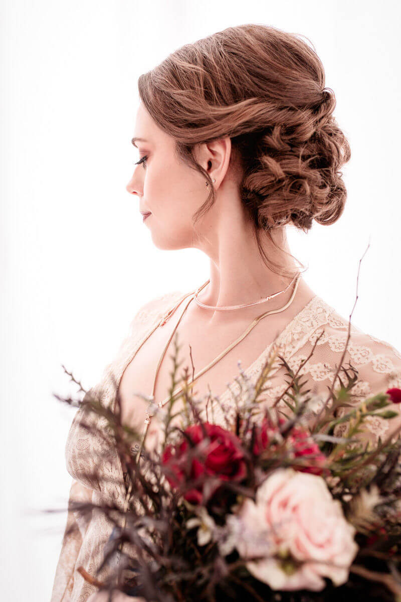 bright and witchy bridal hair and make portrait with bouquet of flowers