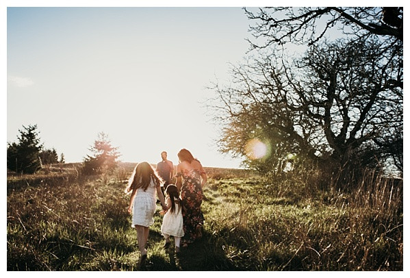 family photos of kids walking away into sunset in grassy field