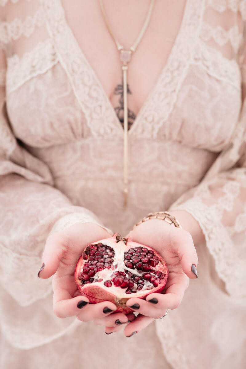 close up photo of pomegrante help by bright and airy greek goddess in fine art portrait